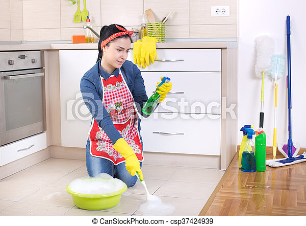 Satisfied and pleasant surprised woman looking at detergent in spray bottle while cleaning kitchen floor with scrubbing brush