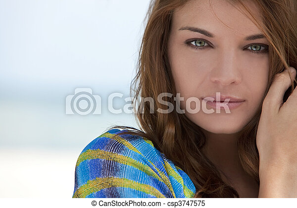 Portrait of a beautiful brunette young woman with stunning green eyes, shot outside in natural light - csp3747575
