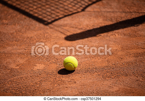 Tennis balls in the shade nets on the ground of clay court
