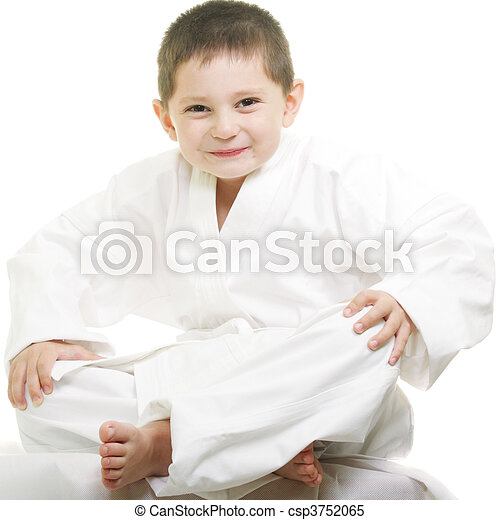 Little karate kid sitting legs crossed against white background