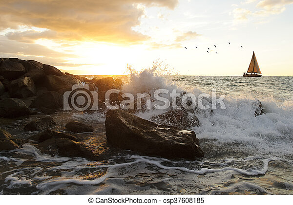 Sailboat waves is an ocean seascape with a wave crashing up against a rock throwing water into the air as a sailboat moves along the ocean horizon..
