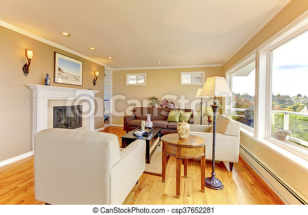 Bright cozy living room with beige walls and fireplace