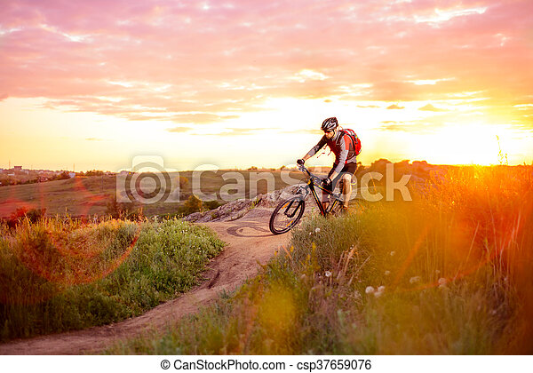 Cyclist Riding the Bike on the Mountain Rocky Trail at Sunset. Extreme Sports