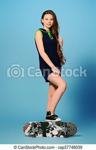 Pretty girl teenager wearing casual clothes posing with her skateboard. Active lifestyle. Studio shot.