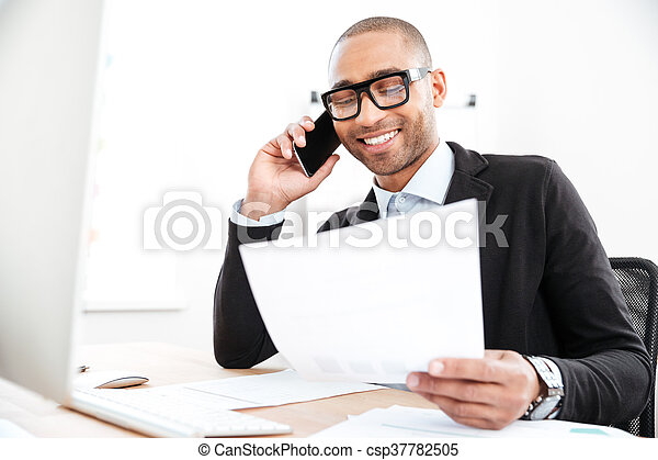Businessman using mobile phone and looking at documents - csp37782505