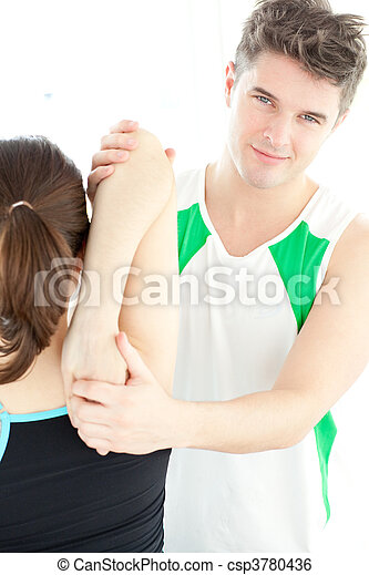 Smiling physical therapist checking a woman's shoulder - csp3780436