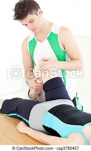 Male physical therapist checking a woman's knee - csp3780457