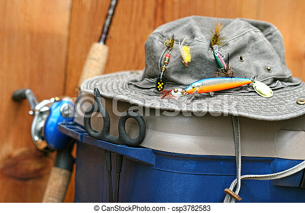 Closeup of fishing tackle box and hat - csp3782583