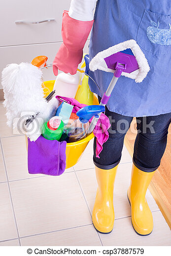 Cleaning lady with apron and gumboots holding basket full of cleaning supplies and equipment in front of kitchen