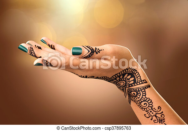 Woman's hand with mehndi tattoo. Hand of Indian bride with black henna tattoos - csp37895763