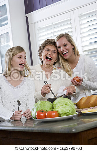 Three generation family in kitchen cooking lunch - csp3790763