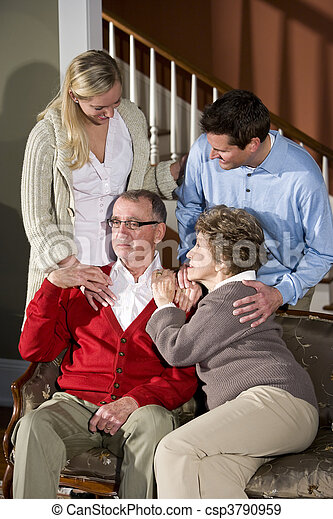 Senior couple on sofa at home with adult children - csp3790959