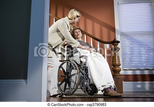 Nurse helping elderly woman in wheelchair at home - csp3790983