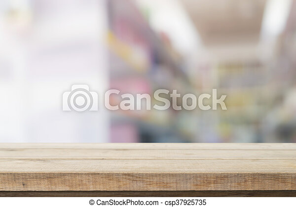 Empty wood table top ready for your product display montage. with book shelf in library blurred background. Blurry perspective view of educational study room space with book shelves