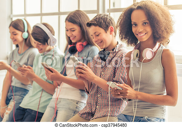 Attractive teenage Afro American girl with headphones is using a smartphone, looking at camera and smiling while sitting among other teenagers
