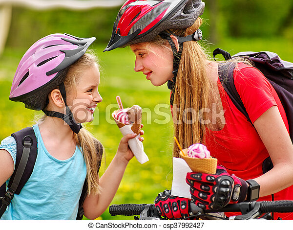 Bicycle girls cycling eating ice cream cone in park.