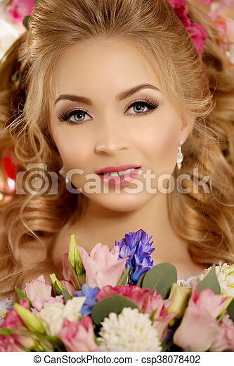 Beautiful fashion model. Sensual bride. Woman with wedding dress, hair and make up. Sweet flowers background. Blue eyes. Natural manicure. Beauty spring girl with bouquet of flowers in hands