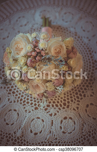 Wedding bouquet of bride - colorful flowers, white roses lying on table. Classic and elegant bridal decoration. close up of wedding bouquet