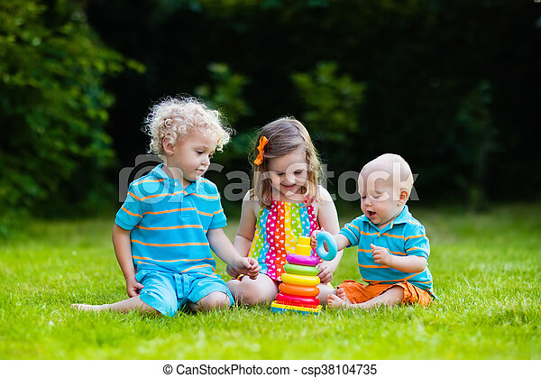 Three little children play with colorful rainbow pyramid toy. Educational toys for young child. Sibling kids building tower together. Toddler boy, preschooler girl and baby build blocks outdoors.