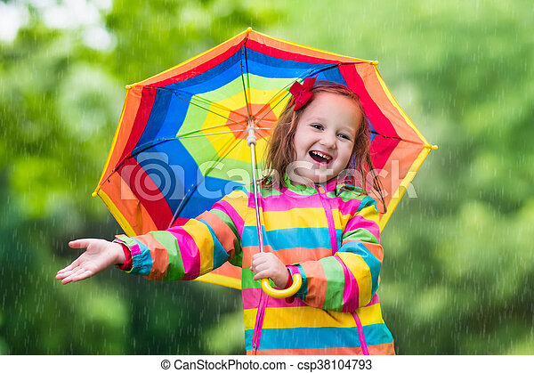 Little girl playing in rainy summer park. Child with rainbow umbrella, waterproof coat and boots jumping in puddle in the rain. Kid walking in autumn shower. Outdoor fun by any weather