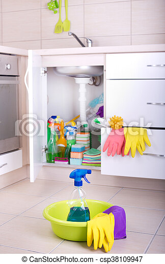 Spray bottle and cleaning tools in washbasin on the kitchen floor. Cleaning supplies and equipment stored in kitchen cabinet in background