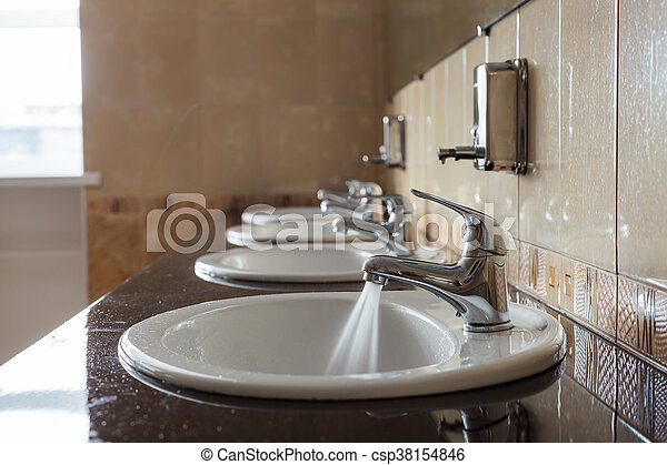 Water flows from the tap in a public toilet. - csp38154846