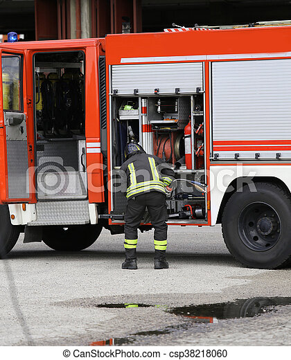 Firefighter prepares the water hoses to put out the fire during a training exercise in fire brigade station