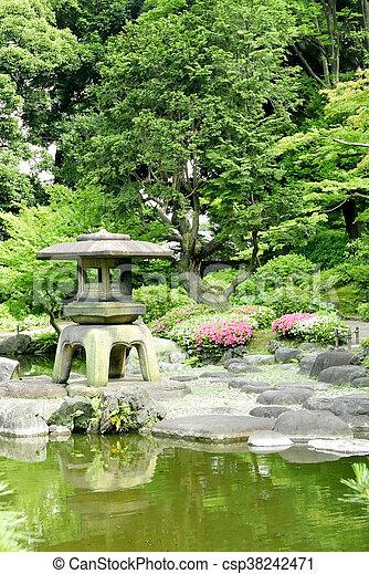 Vertical Japanese outdoor stone lantern, flower plants and lake in the zen garden