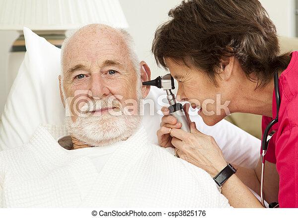 Home Health Nurse Checks Ears - csp3825176