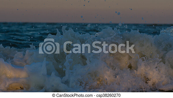 Stormy sunset at the sea. Wave and splash - csp38260270