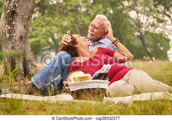 Senior couple, old man and woman in park on weekend activity. Grandpa and grandma doing picnic in wood. Concept of retirement age and love.