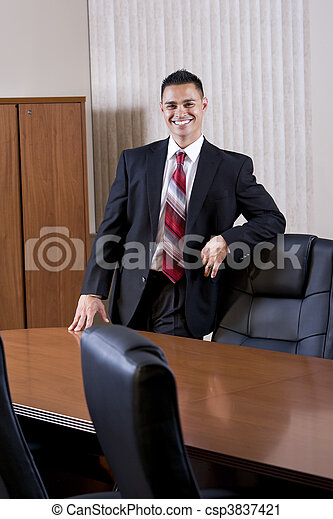 Happy mid-adult Hispanic businessman in boardroom - csp3837421