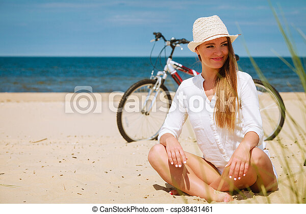 Sport and recreation. Young girl in straw hat resting after cycling on beach. Smiling tourist spending time on seaside. Leisure in summer.