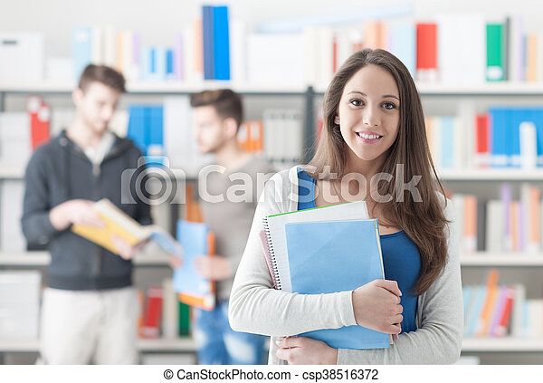 Confident smiling student girl posing in the library, holding notebooks and looking at camera, learning and education concept