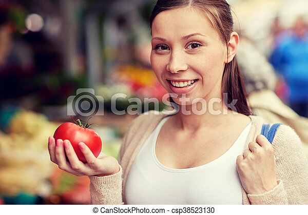sale, shopping, food and people concept - happy woman holding tomato at street market