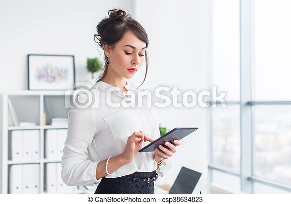 Young smiling female office worker at her workplace reading, browsing news ad messages using tablet computer while having break