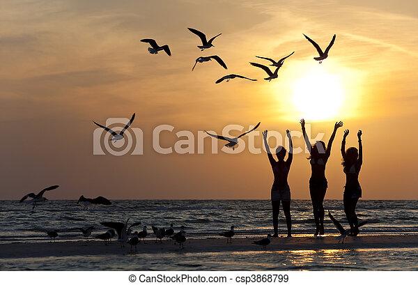 tres, joven, mujeres, bailando, en, playa, en, ocaso - csp3868799
