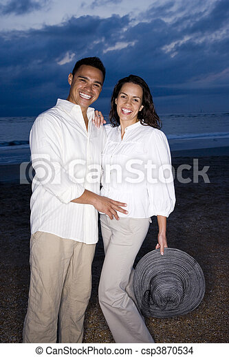 Mid-adult Hispanic couple smiling on beach at dawn - csp3870534