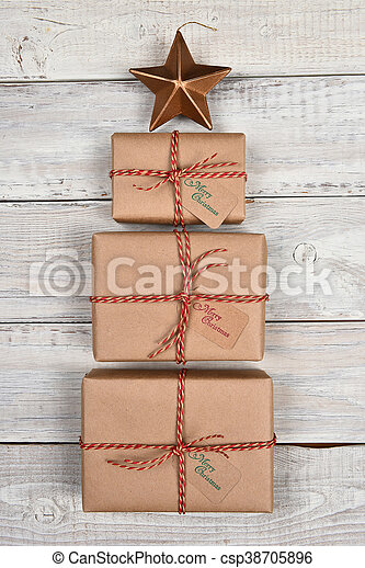 Three plain brown paper wrapped gifts in the shape of a Christmas tree with star. Tied with twine, with gift tags on white rustic wood background.