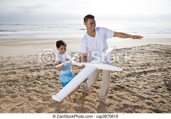 Hispanic dad, girl playing with toy plane on beach - csp3870619
