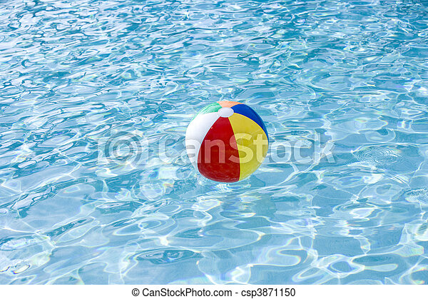 Beach ball floating on surface of swimming pool - csp3871150