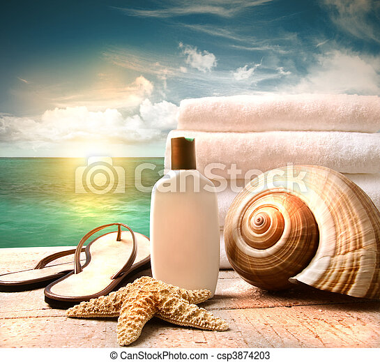 Sunblock lotion and towels and ocean scene - csp3874203