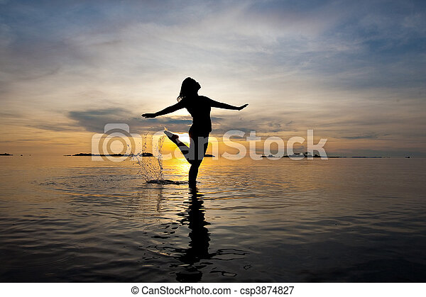 Beautiful silhouette of woman  in shallow water during sunrise - csp3874827