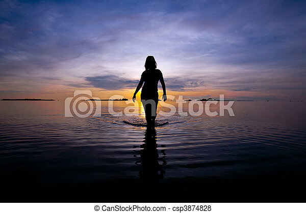 Beautiful silhouette of woman figure walking in shallow sea at sunrise - csp3874828