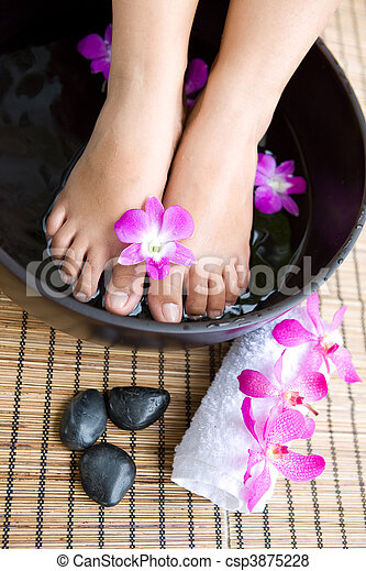 Feminine feet in foot spa bowl with orchids - csp3875228