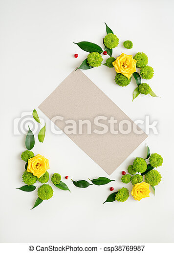 Paper with wreath frame from roses, chamomile and chrysanthemum flowers, ficus leaves and ripe rowan on white background. Overhead view. Flat lay.
