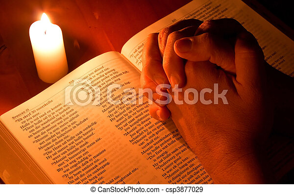 Bible by candle light with hands folded in prayer - csp3877029