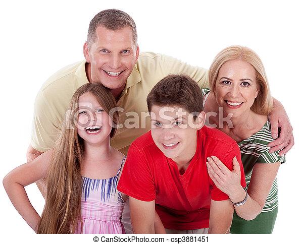 Happy family smiling towards the camera - csp3881451