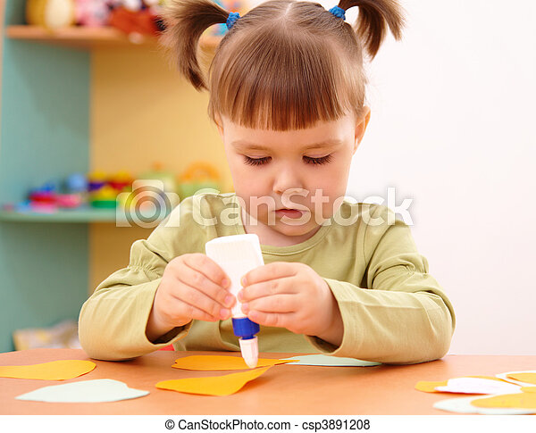 Little girl doing arts and crafts in preschool - csp3891208