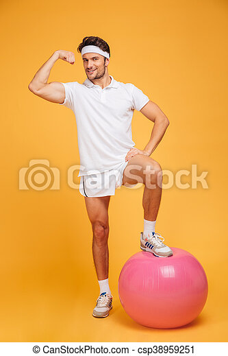Young handsome sportsman with fitness ball showing biceps - csp38959251